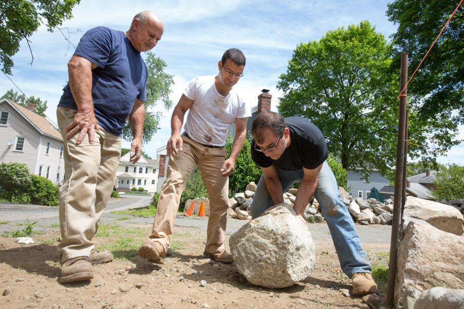 John Umina (center) and his brother Chris Umina (right) and John's father Al Umina moved a stone to build a stone wall.